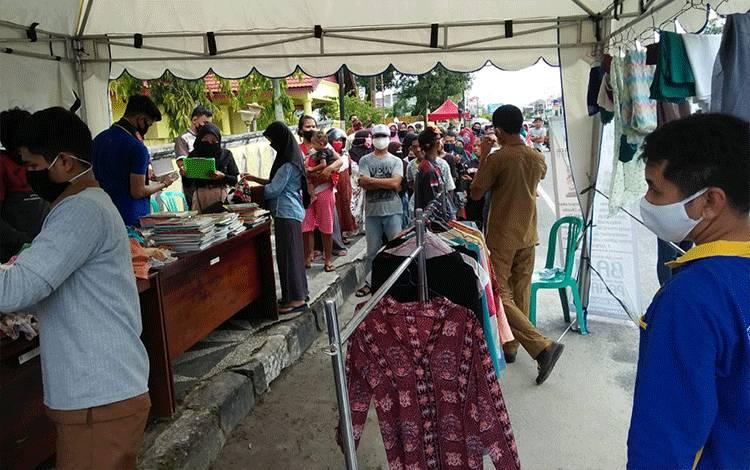Warga mendatangi tempat pembagian pakaian bekas dan buku bacaan gratis dari Diskominfo Kobar dan Kelurahan Raja.