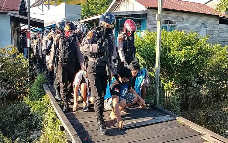 Petugas saat menangkap puluhan orang diduga pengguna narkoba di Jalan Riau Gang Sayur wilayah Puntun Kota Palangka Raya, Selasa 19 Mei 2020 sore.