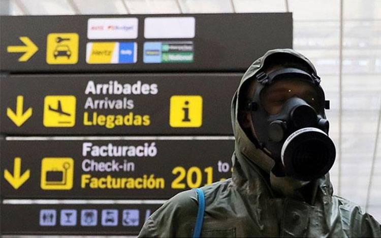 Seorang penumpang pesawat mengenakan pakaian pelindung dan masker gas saat tiba di Bandara Josep Tarradellas Barcelona- El Prat di Barcelona, Spanyol, 15 Mei 2020. REUTERS/Nacho Doce