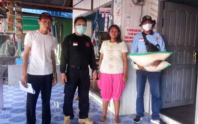 Lurah Kuala Pembuang II saat memantau pendistribusian beras hingga ke warga penerima
