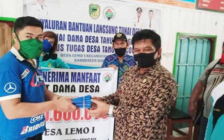 Camat Teweh Tengah, M Mastur didampingi Kades Lemo I Nuripansyah menyerahkan buku rekening dan ATM kepada warga penerima BLT DD