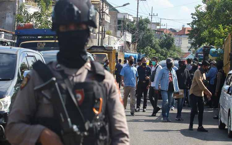Polisi bersenjata berjaga saat Detasemen Khusus (Densus) 88 Antiteror Polri menggeledah sebuah gudang ekspedisi di Jalan Kunti No 72, Surabaya, Jawa Timur, Kamis, 30 April 2020. Gudang ekspedisi itu diduga merupakan tempat kerja terduga teroris JH alias AF. ANTARA/Didik Suhartono