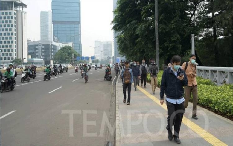 Sejumlah warga melintas di jalur pedestrian Jalan Sudirman, Jakarta, Senin, 16 Maret 2020. (foto : tempo.co)