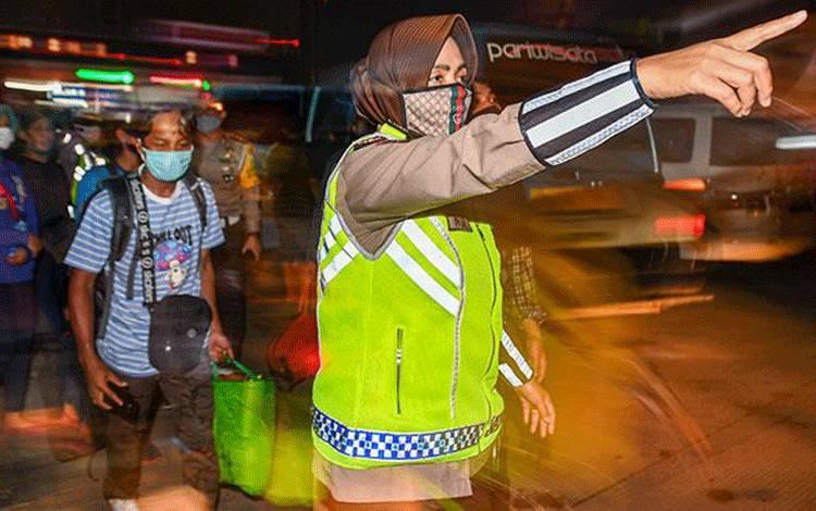 Petugas kepolisian mengarahkan calon pemudik yang terjaring razia penyekatan di Pintu Tol Cikarang Barat, Bekasi, Kamis, 21 Mei 2020. Larangan mudik bagi warga Jakarta dimulai sejak 24 April 2020 lalu. ANTARA/Nova Wahyudi