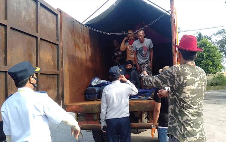 Petugas jaga posko Covid-19 saat mendapati truk yang sengaja mengangkut manusia agar tidak ketahuan membawa penumpang.
