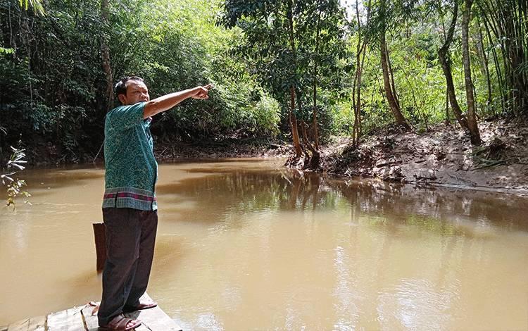 Kepala Desa Haringen, Yasen, saat menunjuk ranting-ranting pohon yang belum dibersihkan di Sungai Sirau.