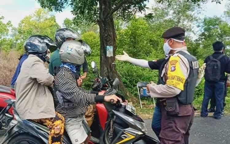 Petugas saat melakukan pemeriksaan sekaligus mengingatkan para pengendara agar tetap menggunakan masker.
