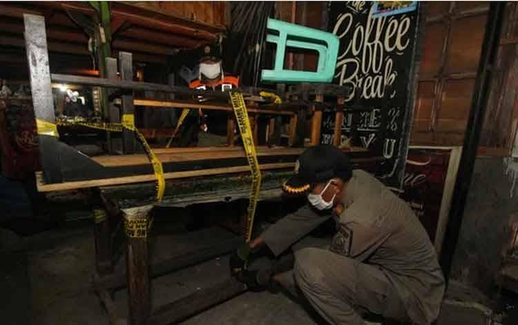 Petugas menyegel meja dan kursi sebuah kafe saat razia pembatasan aktivitas malam hari di kawasan Simo Gunung, Surabaya, Jawa Timur, Sabtu, 9 Mei 2020 malam. Pada hari ke-12 pelaksanaan PSBB di Surabaya, petugas gabungan masih menjumpai sejumlah kafe melanggar pembatasan aktivitas malam hari. ANTARA/Didik Suhartono