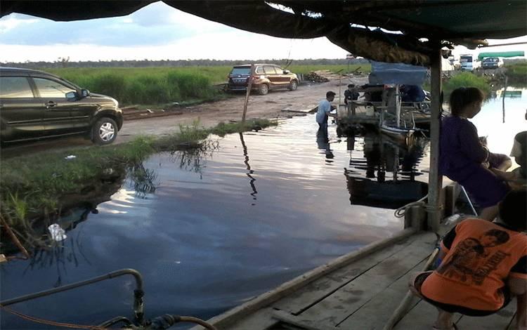 Warga Desa Talingke Kecamatan Tasik Payawan harus menggunakan fery tradisional menuju desa karena jalan masih terendam banjir sepanjang sekitar satu kilometer
