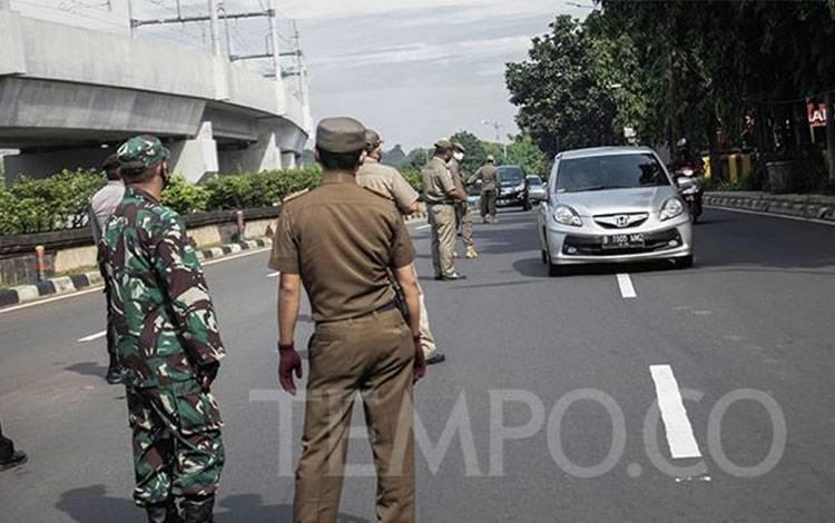 Petugas gabungan melakukan pengecekan Surat Izin Keluar Masuk (SIKM) Jakarta kepada pengendara dengan mobil bernomor polisi luar Jabodetabek di Pos Pemantauan PSBB Pasar Jumat, Jakarta Selatan, Selasa, 26 Mei 2020. TEMPO/M Taufan Rengganis