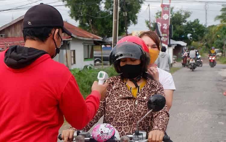 Pemeriksaan suhu tubuh kepada warga yang ingin masuk wilayah Menteng XII Kota Palangka Raya.