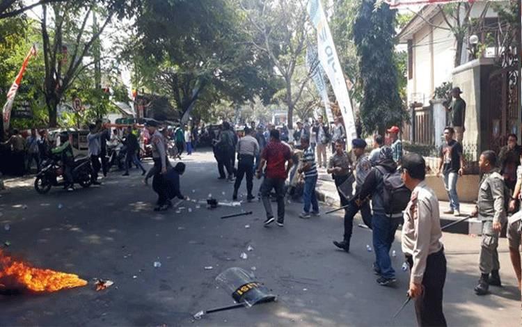 Aksi unjuk rasa mahasiswa di depan Komplek Pemkab Cianjur, Jawa Barat, Kamis 15 Agustus 2019, berlangsung ricuh. Tiga anggota polisi terbakar saat memadamkan api. Tempo/Deden Abdul Aziz
