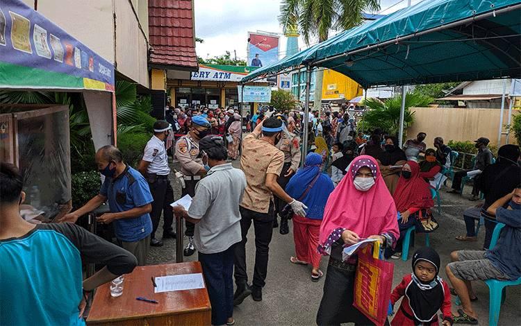 Sejumlah warga yang menerima bantuan tunai dari provinsi dan tidak menerima bantuan memadati halaman Bank Kalteng, Jumat, 29 Mei 2020.
