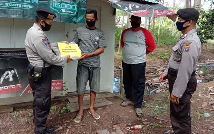 Personel Polsek Kahayan Kuala saat menyalurkan bantuan beras Polri Peduli Covid-19 kepada warga yang kurang mampu