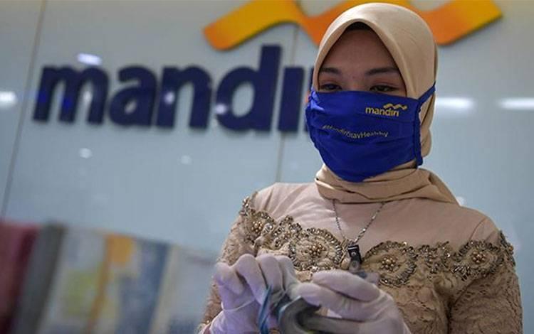 Karyawan Bank Mandiri mengenakan pakaian adat kebaya menghitung uang saat melayani nasabah di salah satu kantor cabang di Jatinegara, Jakarta, Selasa 21 April 2020. ANTARA FOTO/Nova Wahyudi