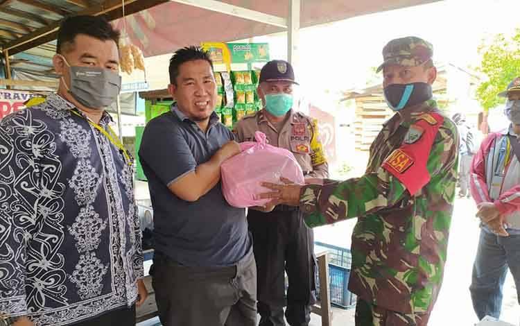 Tim Gugus Tugas Kelurahan Menteng menyerahkan bantuan kepada pria yang viral menyerahkan anaknya di pos PSBB karena mengaku tak mampu beli susu