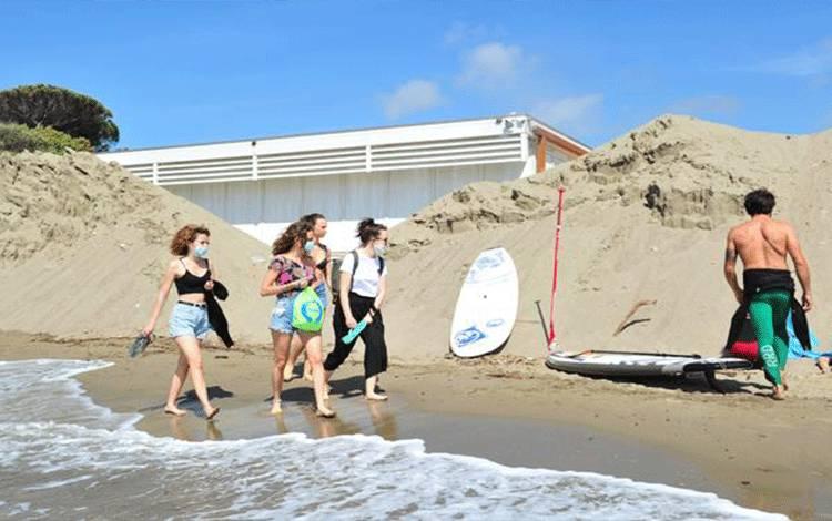 Pengunjung mengenakan masker saat berjalan di sebuah pantai di Castiglione della Pescaia, Italia, 9 Mei 2020. Warga mulai jalan-jalan keluar rumah saat Italia mulai melonggarkan aturan lockdown di tengah wabah virus Corona. REUTERS/Jennifer Lorenzini