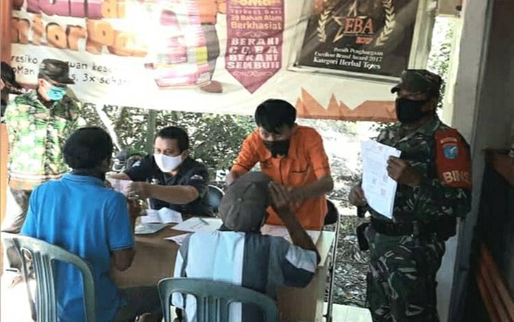 Personel Koramil Sei Tatas saat mengawal penyaluran bantuan sosial tunai di Kecamatan Pulau Petak.