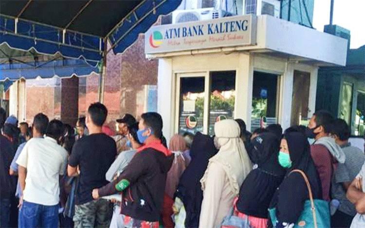 Masyarakat terlihat tidak jaga jarak ketika ingin mengambil bantuan langsung tunai di Bank Kalteng.