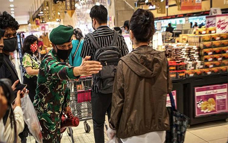 Personel TNI memberikan imbauan kepada pengunjung untuk tetap menjaga jarak di AEON Mall, Tangerang, Banten, Jumat 29 Mei 2020. Sejumlah aturan protokol kesehatan penyebaran COVID-19 diterapkan di pusat perbelanjaan tersebut seiring memasuki era normal baru di tengah pandemi COVID-19. ANTARA FOTO/Fauzan