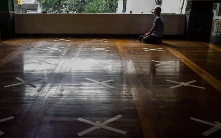 Pengurus Dewan Kemakmuran Masjid (DKM) menunaikan shalat di antara tanda silang antar saf di Masjid Agung Al Ukhuwah, Bandung, Jawa Barat, Senin, 1 Juni 2020. Pemkot Bandung membolehkan tempat ibadah dan restoran dibuka kembali dengan syarat 30 persen dari kapasitas fasilitas tersebut. ANTARA/Novrian Arbi