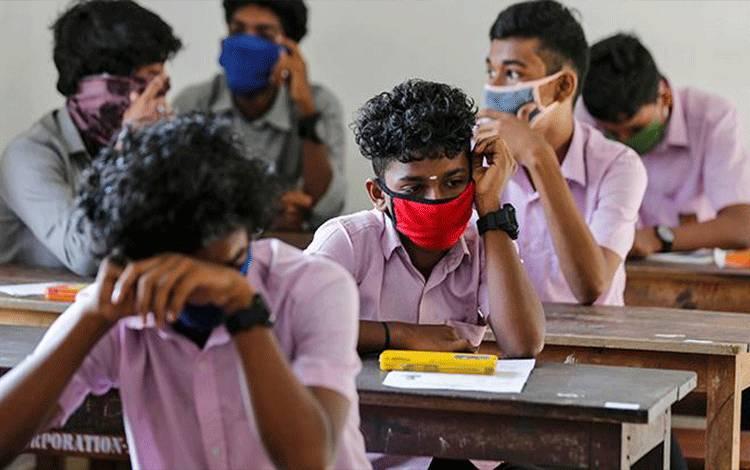 Ilustrasi anak-anak sekolah mengenakan masker saat belajar. (foto : REUTERS/Sivaram V via teras.id)