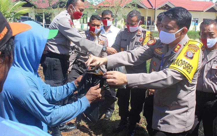 Kapolres Seruyan AKBP Agung Tri Widiantoro saat menyerahkan ikan hasil panen kepada masyarakat.