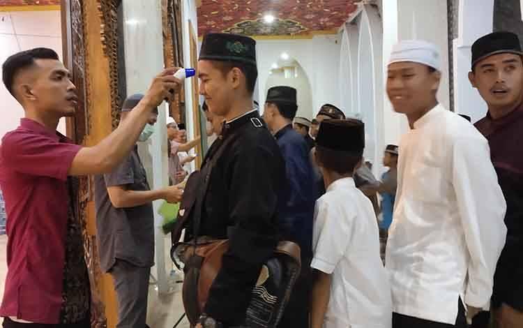 Jamaah Masjid Agung Sukamara saat diperiksa suhu tubuhnya.