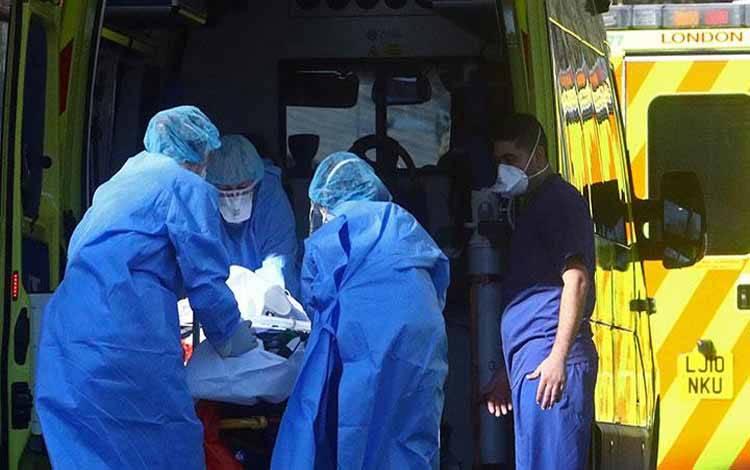 Staf medis menangani pasien di ambulans di RS St Thomas's, saat wabah virus corona Covid-19 di London, Inggris, 26 Maret 2020. REUTERS/Hannah McKay
