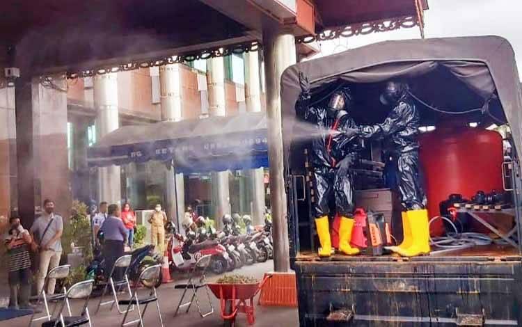 Anggota Satbrimob Polda Kalteng menyemprotkan cairan disinfektan di lingkungan Kantor Bank Kalteng
