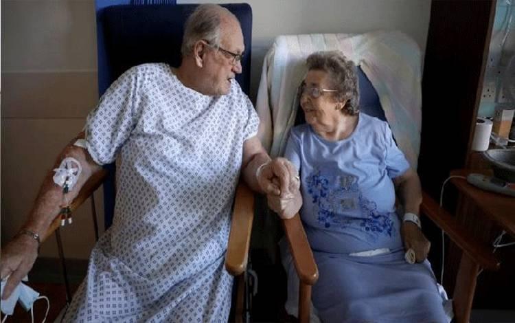 Pasien terinfeksi virus corona George Gilbert, 85 dan istrinya Domneva Gilbert, 84, saling berpegangan tangan saat kunjungan singkat karena dirawat di tempat terpisah, keduanya dalam uji TACTIC-R, di rumah sakit Addenbrooke di Cambridge, Inggris, Kamis (21/5/2020). (REUTERS/POOL)