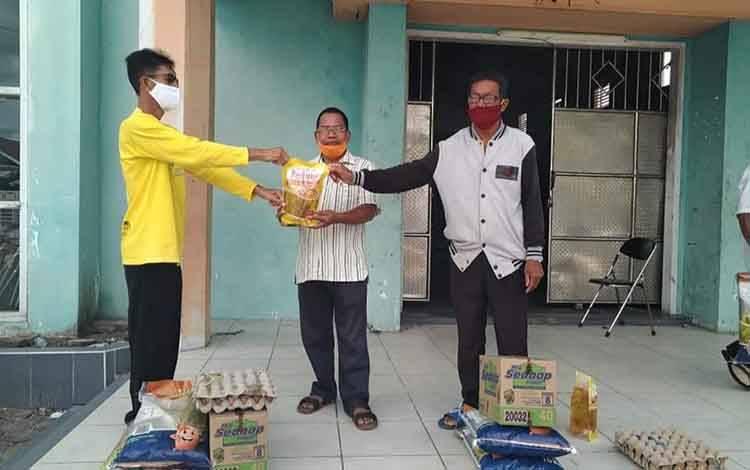 Simbolis, Lurah Mendawai M Zulhadi (kaos kuning) distribusikan bansos tahap kepada wargannya.
