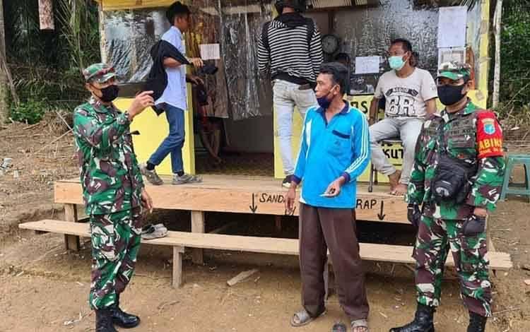 Danramil 1014 - 04/Pangkut Lettu Czi Yunus, saat memantau Pos Pemantauan Covid-19 di pintu masuk Kecamatan Aruta dan meminta setiap warga wajib lapor.