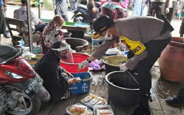 Kapolres Kapuas AKBP Manang Soebeti saat bertemu dengan seorang pedagang keripik gunakan face shield untuk cegah covid-19 di pasar Kapuas pada Rabu, 3 Juni 2020.
