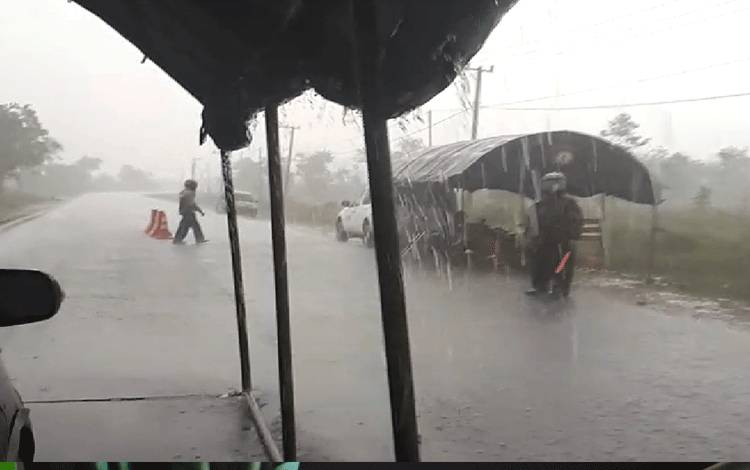 Personel lintas batas Palangka Raya nampak sedang berjaga di tengah jalan meski sedang diguyur hujan deras.