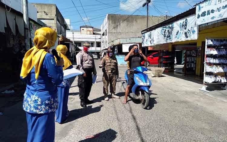 Petugas Puskesmas Ketapang I Sampit dan kepolisian saat memberikan masker dan juga melakukan penyuluhan pencegahan Covid-19.