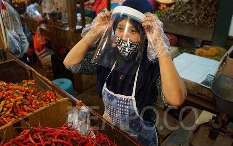 Salah satu pedagang menggunakan face shield dan sarung tangan saat melayani pembeli di Pasar Senen, Jakarta, Senin, 1 Juni 2020. Kementerian Perdagangan menyiapkan pedoman bagi penyelenggara kegiatan perdagangan untuk diterapkan pada saat new normal. TEMPO/Muhammad Hidayat