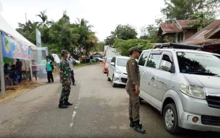 Anggota Satpol PP bersama Polri dan TNI saat memberhentikan mobil-mobil yang melintas di perbatasan untuk dilakukan pemeriksaan kesehatan.