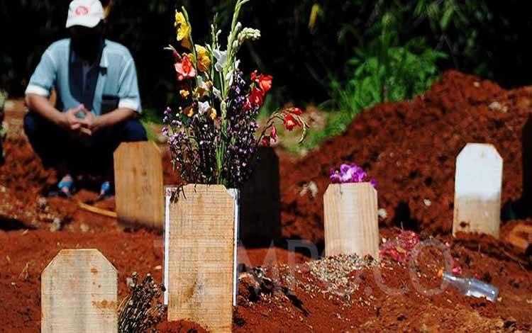 Warga tengah berziarah dipemakaman dengan protokol Covid-19 di TPU Jombang, di Tangerang Selatan, Banten 25 Mei 2020. Untuk melakukan ziarah kubur pada masa pandemi Covid-19, TPU Jombang menerapkan aturan saat berziarah dengan mengenakan masker, cuci tangan saat keluar masuk pemakaman serta dibatasi maksimal 5 orang dan dibatasi waktunya 10 menit bergantian dengan peziarah lainnya. TEMPO/Nurdiansah
