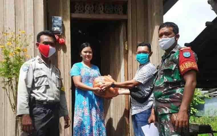 Babinsa Koramil 1016-01/Pahandut, Sertu Dasril bersama Bhabinkamtimas Aipda Tutut Ariwibowo saat mengawal pendistribusian bantuan sembako.