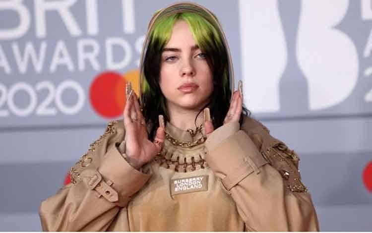 Billie Eilish berpose saat menghadiri Brit Awards di O2 Arena, London, Inggris, 18 Februari 2020. Penyanyi 18 tahun itu tampil unik mengenakan busana dari koleksi Burberry dari ujung kepala sampai ujung kaki. REUTERS/Simon Dawson