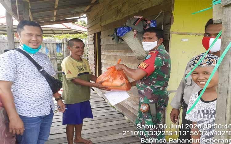 Babinsa Kelurahan Pahandut Seberang menyerahkan bantuan sembako kepada warga kurang mampu terdampak Covid-19