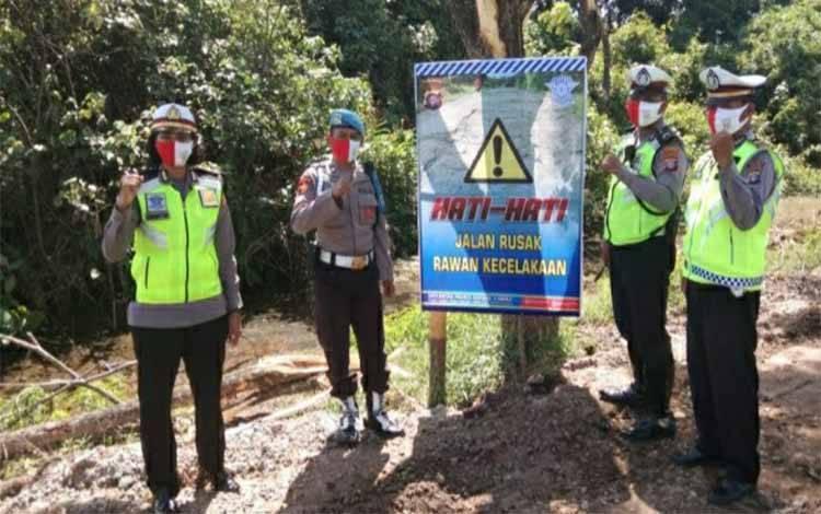 Personel Satlantas Polres Kapuas memasang spanduk imbauan di Jalan Trans Kalimantan, Jalan Jepang Kuala Kapuas