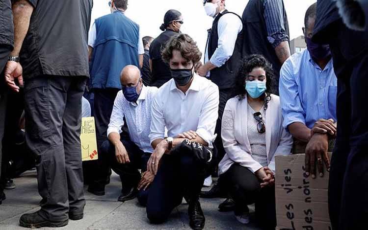 Perdana Menteri Kanada Justin Trudeau mengenakan masker sambil berlutut saat ikuti aksi damai menentang kematian seorang pria berkulit hitam George Floyd, oleh petugas kepolisian Minneapolis, di Parliament Hill, di Ottawa, Ontario, Kanada, 5 Juni 2020. REUTERS/Blair Gable