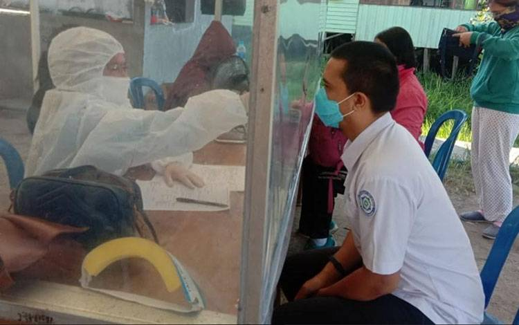Petugas Kesehatan Gugus Tugas Covid-19 Pulang Pisau saat mengukur suhu tubuh warga.