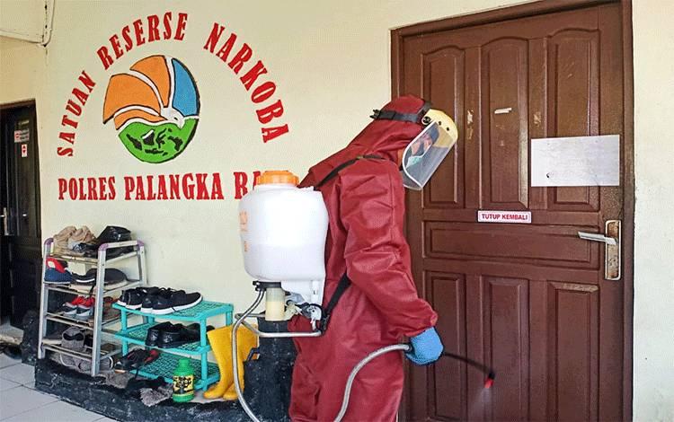 Petugas saat melakukan penyemprotan cairan disinfektan di seluruh ruangan kerja Polresta Palangka Raya, Selasa 9 Juni 2020.