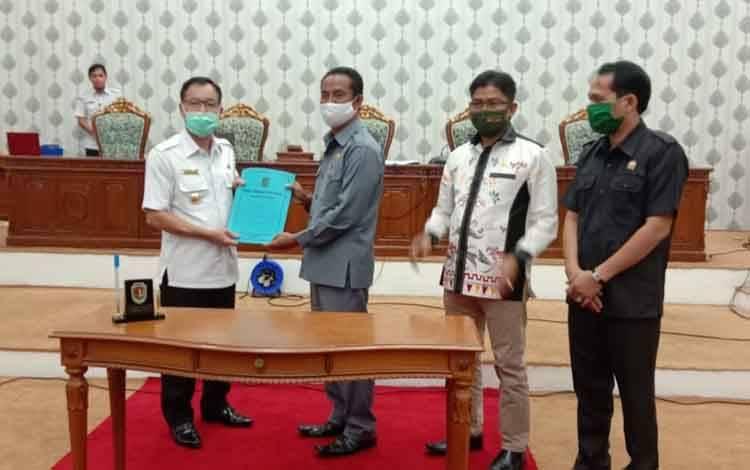 Bupati Katingan Sakariyas menerima dokumen raperda dari Ketua DPRD Marwan Susanto.