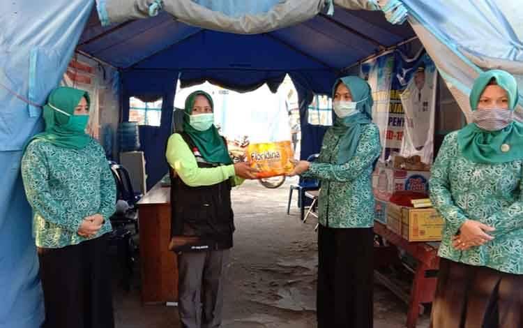Ketua TP PKK Sukamara, Siti Zulaiha Windu Subagio saat menyerahkan bantuan kepada petugas posko di Pelabuhan Tangsi.
