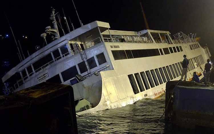 Warga mengamati KMP Dharma Rucitra III yang berada dalam posisi miring di Dermaga 2 Pelabuhan Padangbai, Karangasem, Bali, Sabtu 13 Juni 2020 dini hari. Kapal yang mengangkut sekitar 60 penumpang dan ABK serta puluhan kendaraan berbagai jenis dari Pelabuhan Lembar, Lombok, tersebut diduga mengalami kebocoran lambung kapal. ANTARA FOTO/Fikri Yusuf