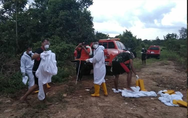 Petugas melepas APD usai menguburkan jenazah Ny KW, Sabtu 13 Juni 2020.